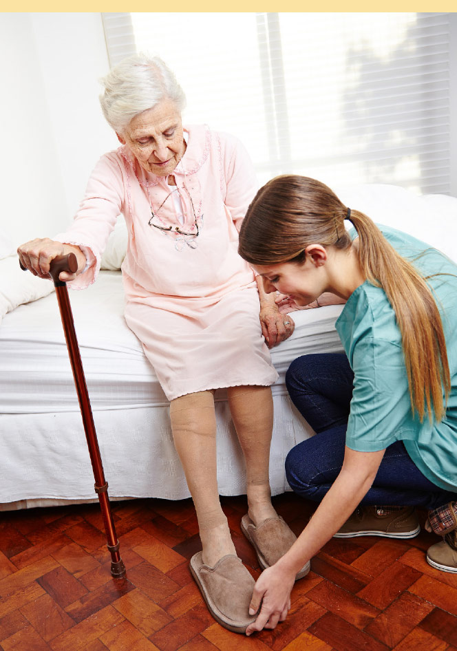 Helping elderly patient put on her slippers