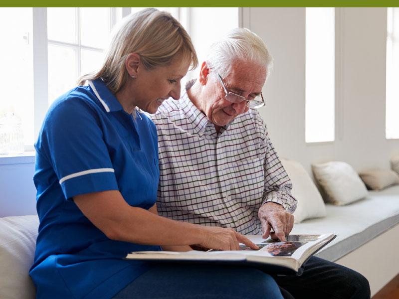 Woman looking through photo book memories with elderly patient