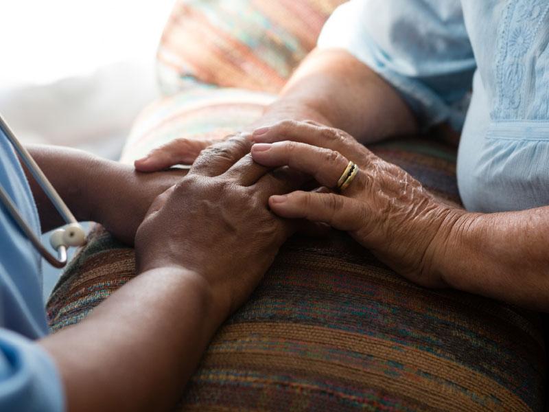 Nurse comforting elderly patient