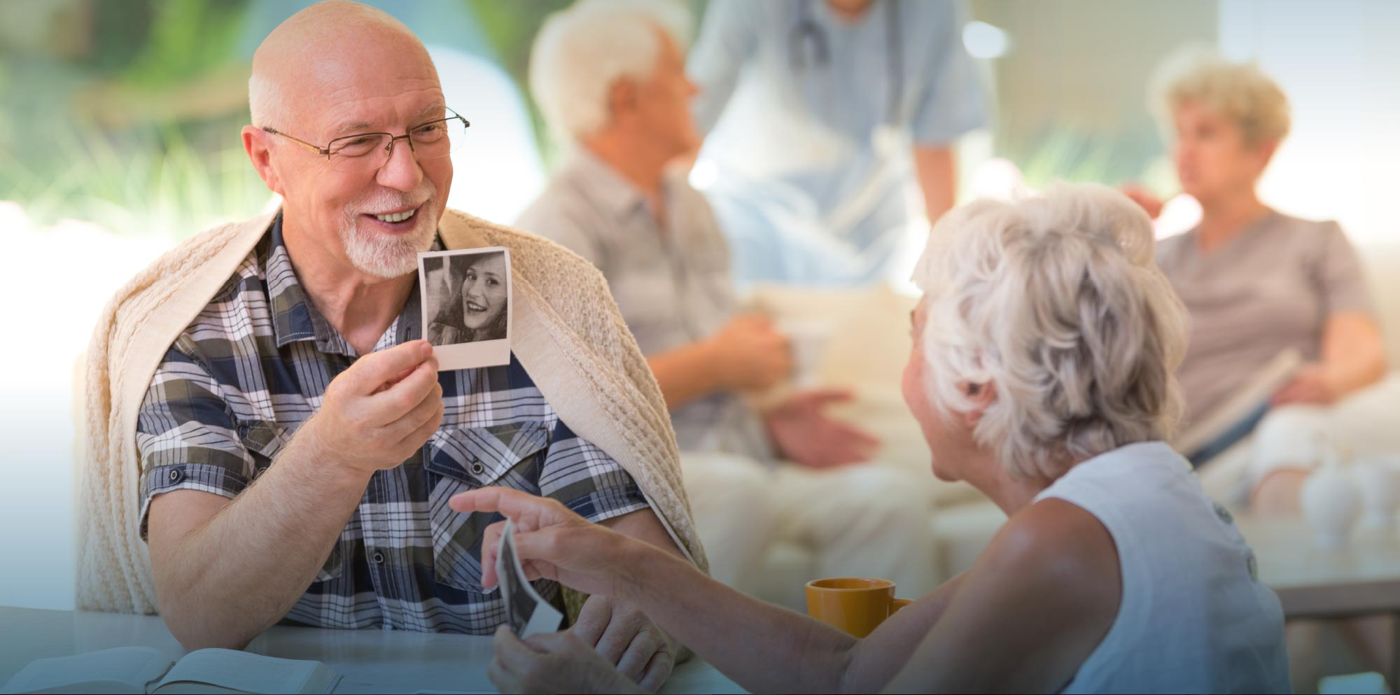 Middle aged man sharing polaroids with elderly mother